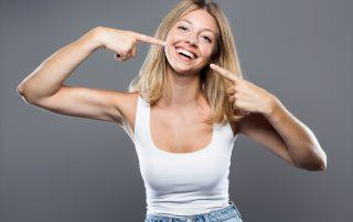 Girl pointing at white teeth